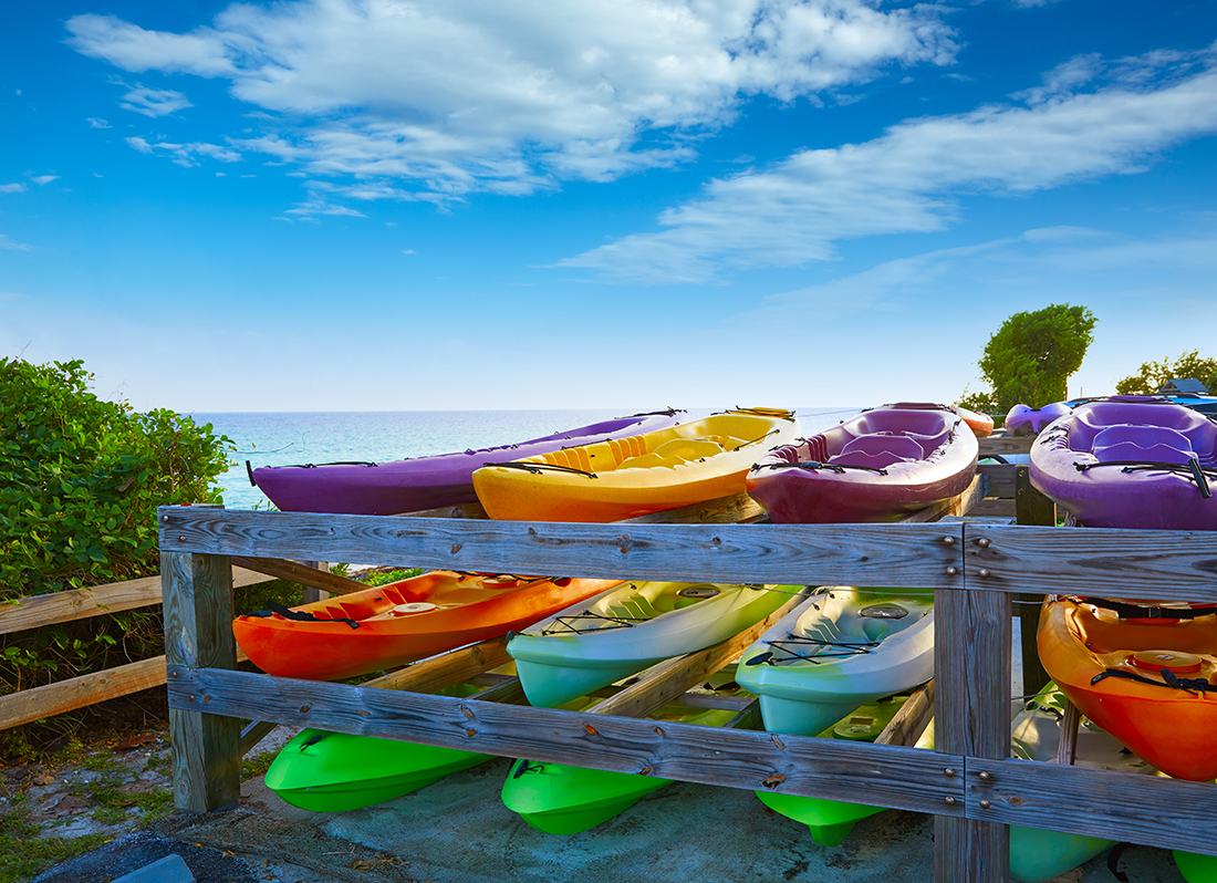 Nine colorful kayaks on a rack at the beach.