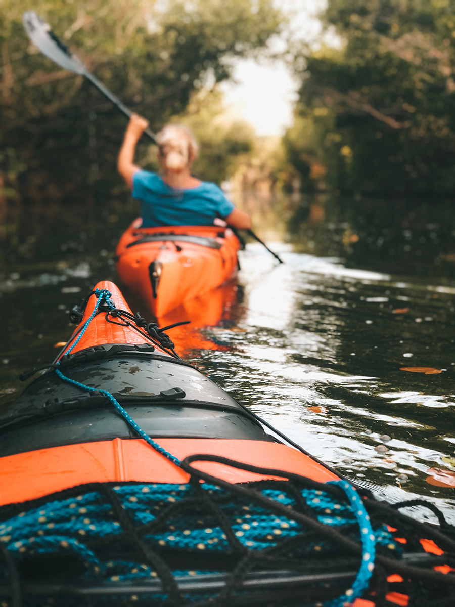 A woman paddling an orange kayak with the tip of another kayak behind her.